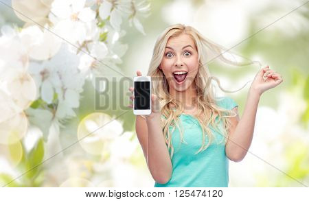 emotions, expressions, technology and people concept - smiling young woman or teenage girl showing blank smartphone screen over natural spring cherry blossom background