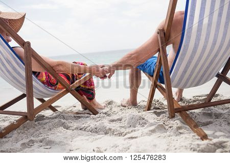Rear view of senior couple sitting on deckchairs and holding hands while relaxing on the beach