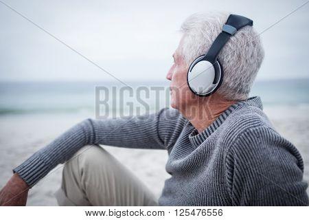 Senior man listening to music on headphone at beach