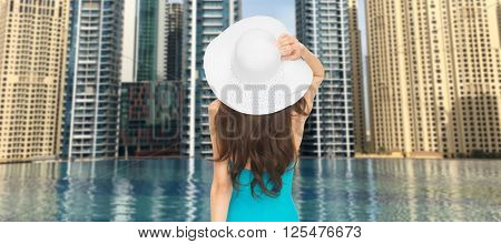 people, summer holidays, travel, tourism and vacation concept - woman in swimsuit and sun hat from back over dubai city and infinity edge pool background