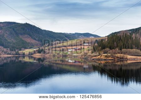 Rural Norwegian Landscape With Still Lake Water
