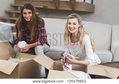 Portrait of friends unpacking carton boxes in their new house