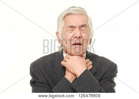 studio shot of senior Japanese businessman having throat pain