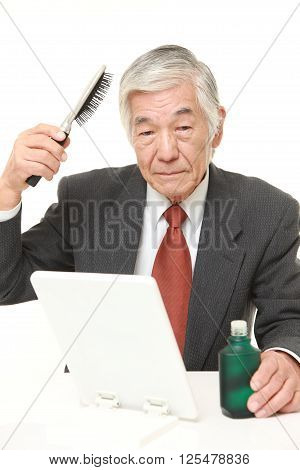 studio shot of senior Japanese businessman using hair restorer