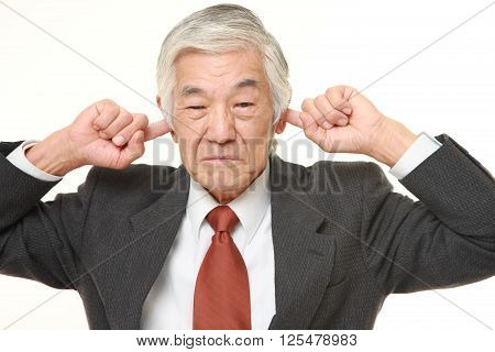 studio shot of senior Japanese businessman suffers from noise