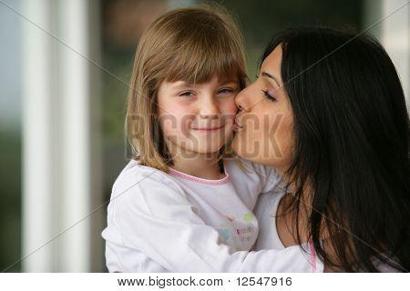 Retrato de uma jovem mulher carregando e beijando uma menina