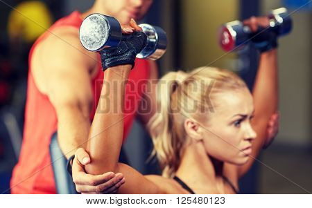 sport, fitness, bodybuilding, lifestyle and people concept - man and woman with dumbbells flexing muscles in gym