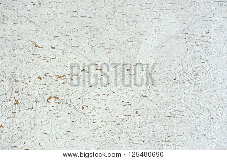 An old light grey cracked painted wall as a background