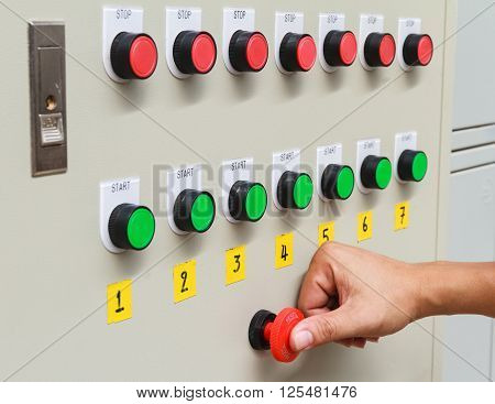 Thumb touch on red emergency stop switch and green start button