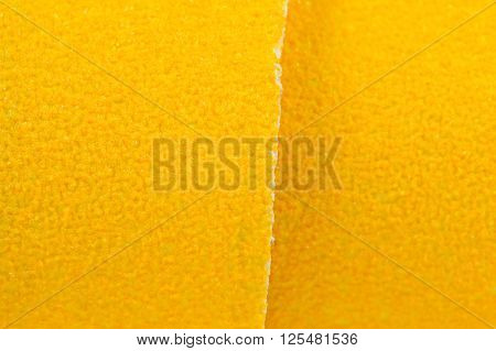 A macro shot of bright yellow sandpaper