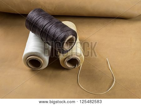 thread for leather crafts three coils on brown leather