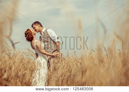 Happy Kissing Couple On The Wheat Field Background.