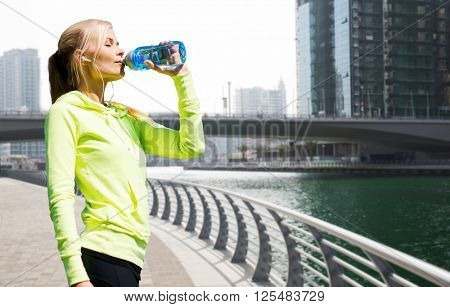 fitness, sport, people and healthy lifestyle concept - woman drinking water after doing sports over dubai city street or waterfront and bridge background