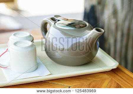 Closeup of tea cup and tea pot on wood floor background