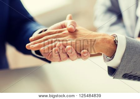people, homosexuality, same-sex marriage and love concept - close up of happy male gay couple hands with wedding ring on