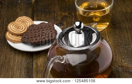 Glass cup of green tea and teapot with various cookies on wooden background