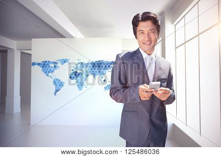 Confident estate agent standing at front door texting against background with hexagons and world map