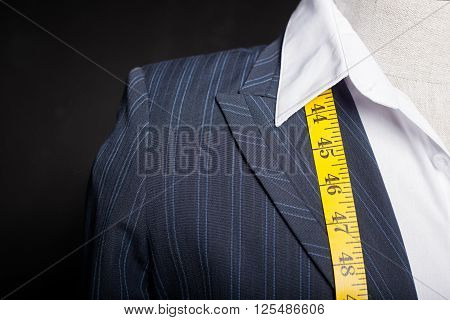 Tailors mannequin with measure tape around it