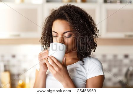 Revel in taste. Positive nice delighted girl holding cup and drinking tea while enjoying it in the kitchen