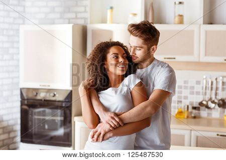 Fervent love. Content positive young couple embracing and looking at each other while expressing their feelings