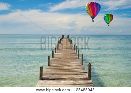 Summer Travel Vacation and Holiday concept - Colorful hot-air balloons flying over Wooden pier in Phuket Thailand