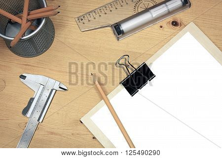 Blank white paper on wooden table with technical tools ruler caliper pencils holder