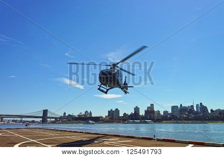 Helicopter and Brooklyn bridge and Manhattan bridge over East River on the background. Bridges connect Lower Manhattan with Brooklyn of New York USA. Brooklyn Heights on the background.