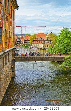 BAMBERG GERMANY - MAY 9 2013: Old city hall and Bridge over Regnitz River in Bamberg in Germany. View to fisherman houses in Little Venice. People nearby