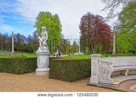 POTSDAM GERMANY - APRIL 30 2013: Sculpture in Sanssouci Park in Potsdam in Germany. It used to be a summer palace of King of Prussia Frederick the Great. People around