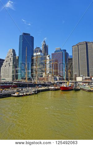 New York City, USA - April 25, 2015: Ships at the harbor of South Street Seaport on East River. Lower Manhattan in New York USA is on the background. Pier 17. Tourists around.