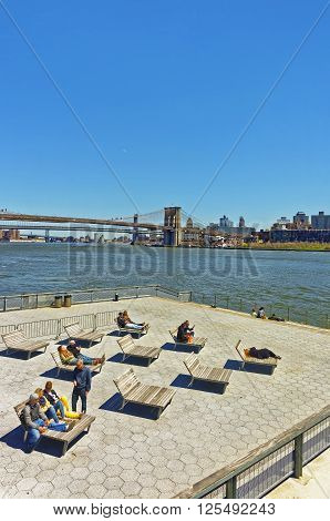 NEW YORK USA - APRIL 25 2015: Tourists relaxing on sunbeds on Pier in Lower Manhattan New York. View from Ferry on Pier Brooklyn Bridge and Manhattan Bridge and Brooklyn Heights USA East River