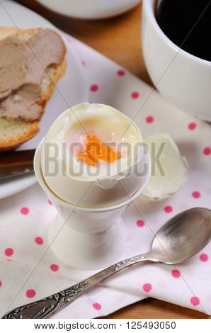 Eggs boiled in pashotnitse for breakfast with a cup of coffee and liver pate