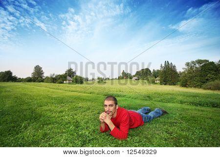 Man Lying On Green Grass In Beautiful Landscape