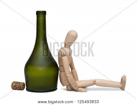Hard drinking. The lay figure sits near a bottle with alcohol isolated on the white background. With shadow.