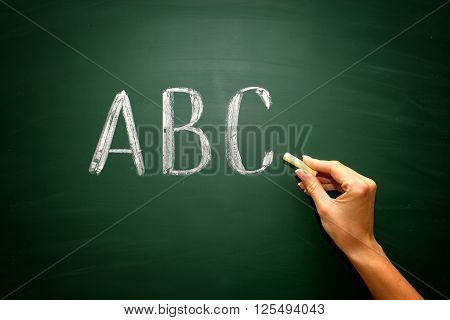 abc letters with hand and chalk on blackboard