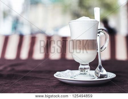 Photo of the cup with latte on a table
