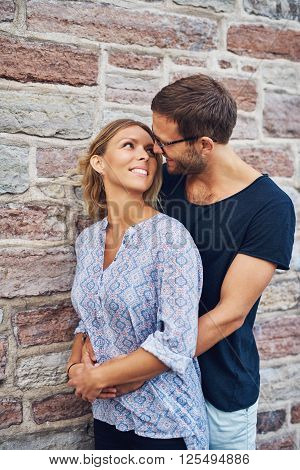 Romantic Couple Smiling Each Other Against Wall