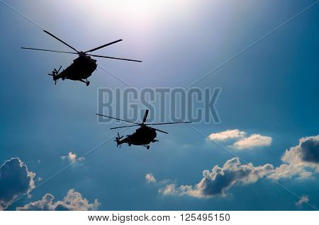 silhouette of two transport helicopters flying in the sky