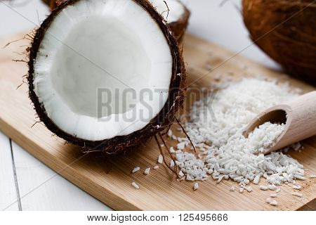 Whole and broken coconut with grated cocont flakes.