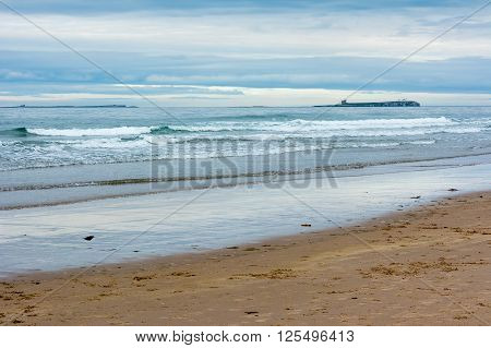 Peaceful evening coastal scene at Bamburgh and Farne Islands England