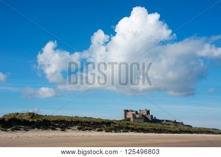 View of Bamburgh Castle in the distance under a blue sky with cumulus clouds