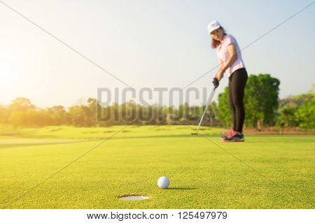 Asian woman golfer putting on green for birdie while on vacation