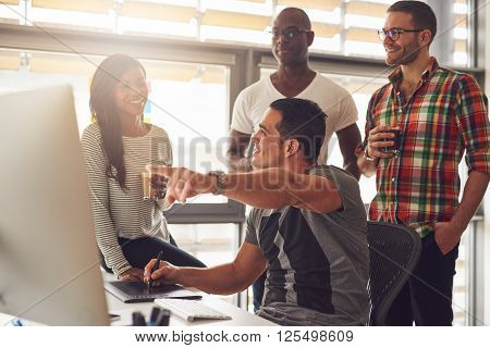 Man Showing Something On His Computer To A Group