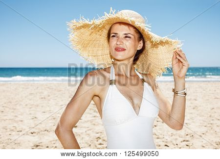 Woman In Swimsuit And Straw Hat At Beach Looking Into Distance