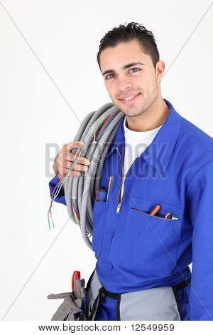 Young electrician carrying a cable on white background