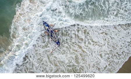 Aerial view of people pushing a rowboat out into the ocean