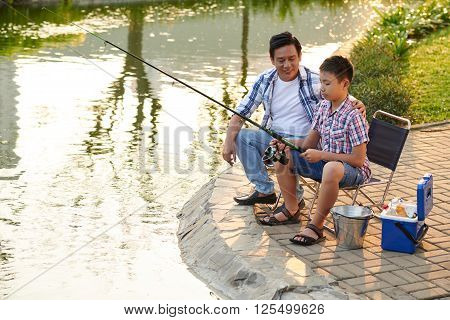 Proud father teaching his son fishing in tha park