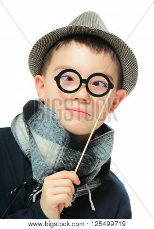 Funny portrait of boy wearing a hat with party glasses on white background