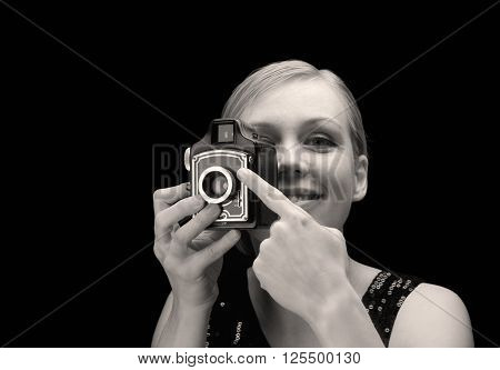 Black and white picture of a young blonde woman holding a retro photo camera and smiling