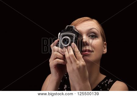 Young blonde woman holding a retro photo camera